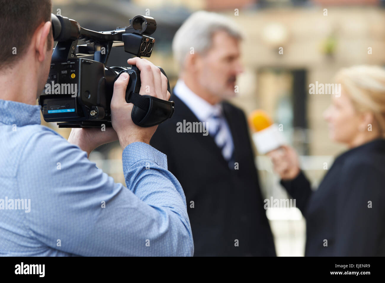 Cameraman Recording Female Journalist Interviewing Businessman - Stock Image
