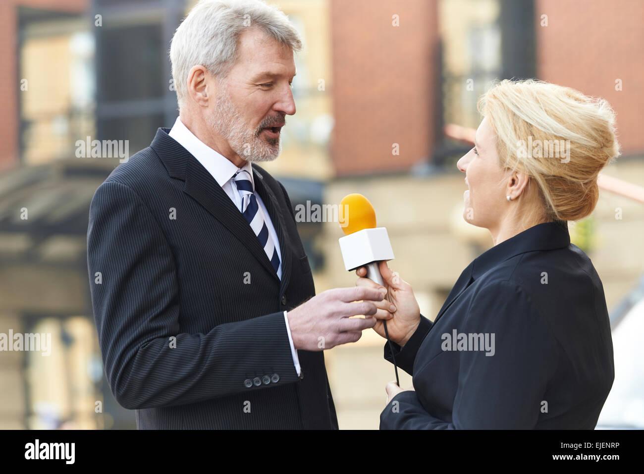 Cameraman Recording Female Journalist Interviewing Businessman - Stock Image