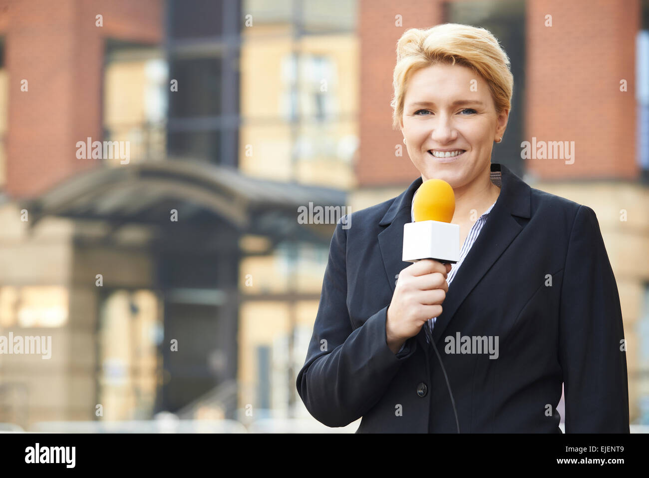 Female Journalist Broadcasting Outside Office Building - Stock Image