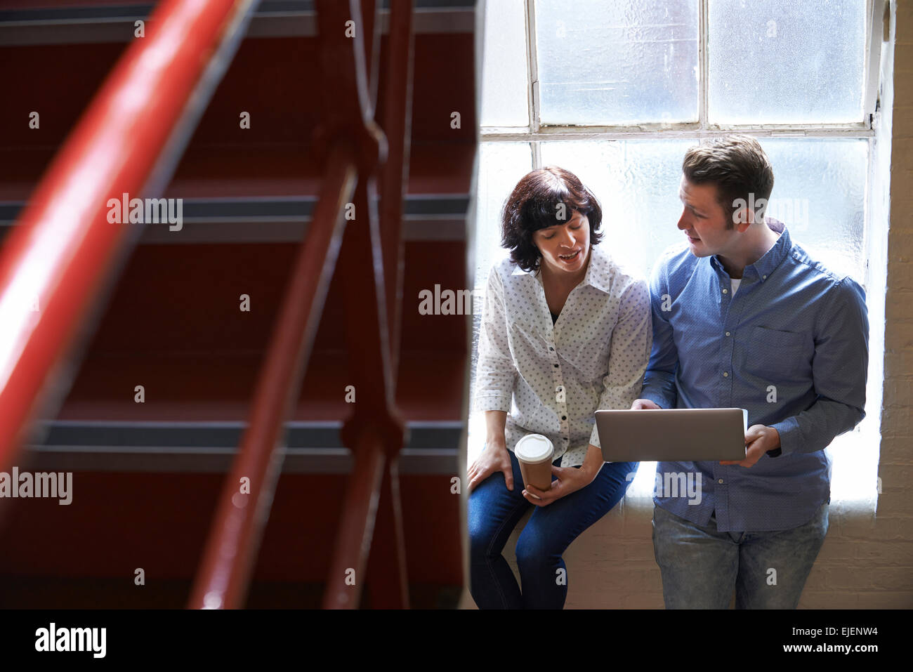 Two Businesspeople Having Informal Meeting On Office Stairs Stock Photo