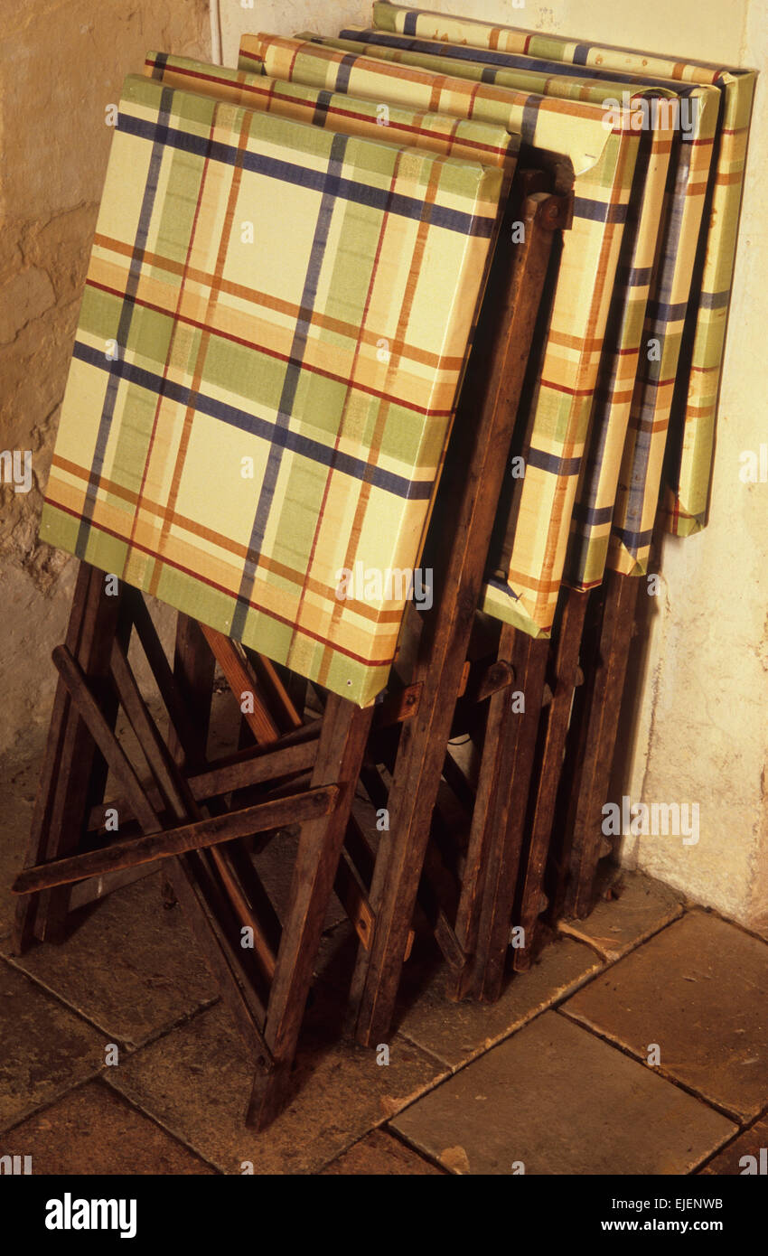 Vintage folding brown wooden picnic tables with new check plastic top covers stacked in row against wall - Stock Image