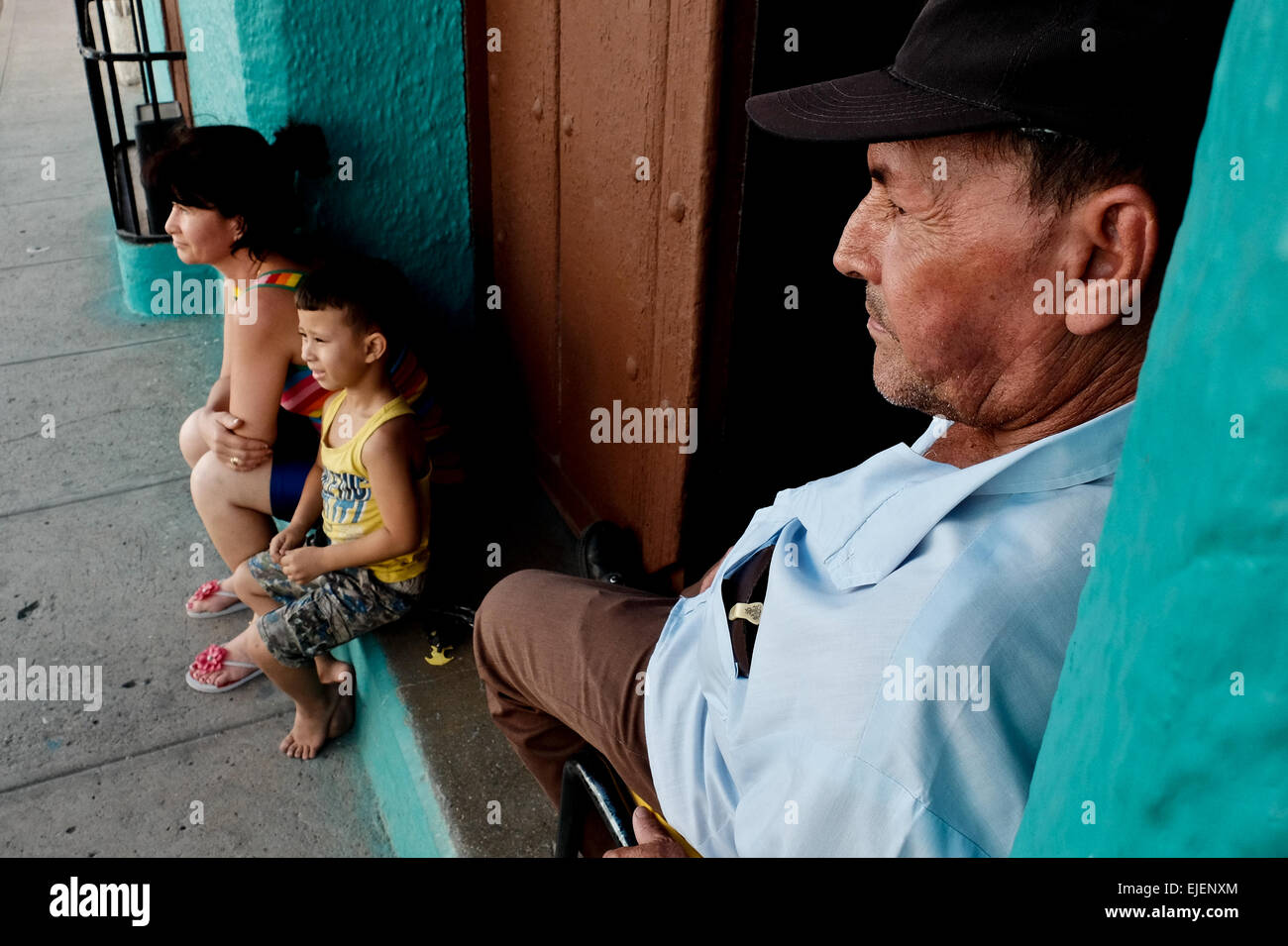 A man watches over his family on the doorstep to their home in the 500 year old city of Sancti Spiritus, Cuba. Cubans - Stock Image