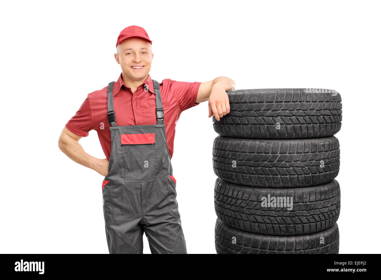 Male mechanic in a red shirt and gray jumpsuit leaning on a stack of tires isolated on white background - Stock Image