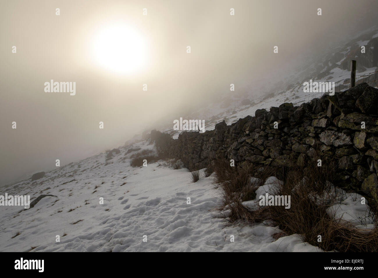 Sun shining sunshine burning through low cloud with snow on ground in winter. Ogwen Valley, Snowdonia National Park, - Stock Image
