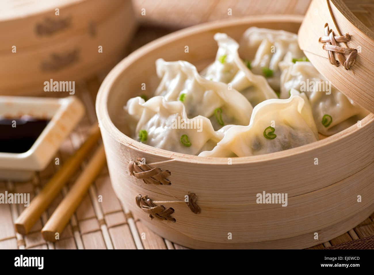Dim sum with leeks, meat, and green onions in a bamboo steamer. - Stock Image