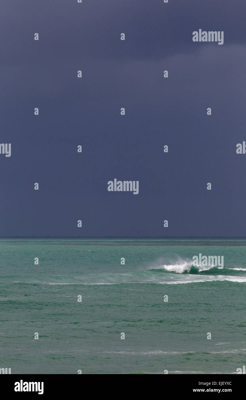 Background of sea and sky, dark stormy sky and aquamarine water with wave - Stock Image