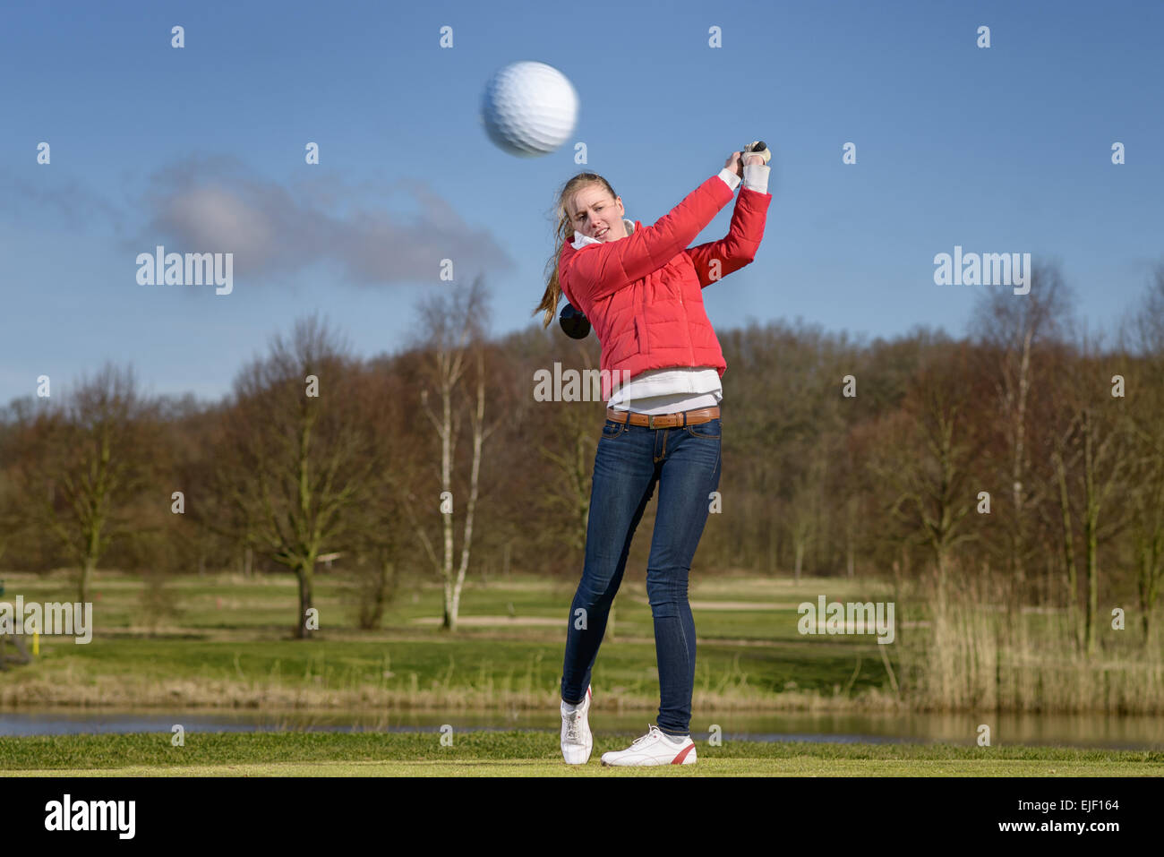 Woman golfer hitting the golf ball with a driver in front of a water hazard on a golf course with the ball flying - Stock Image