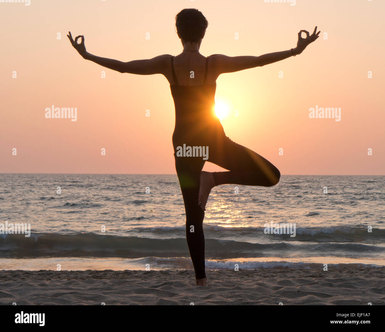 A woman practicing yoga on a beach at sunset - Stock Image