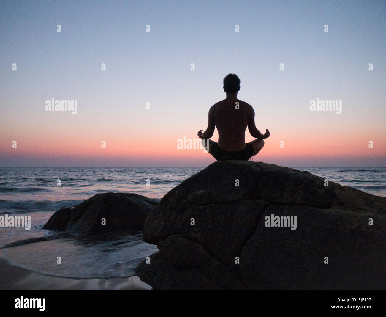 A man in meditation on a beach in Goa India at sunset as venus rises - Stock Image