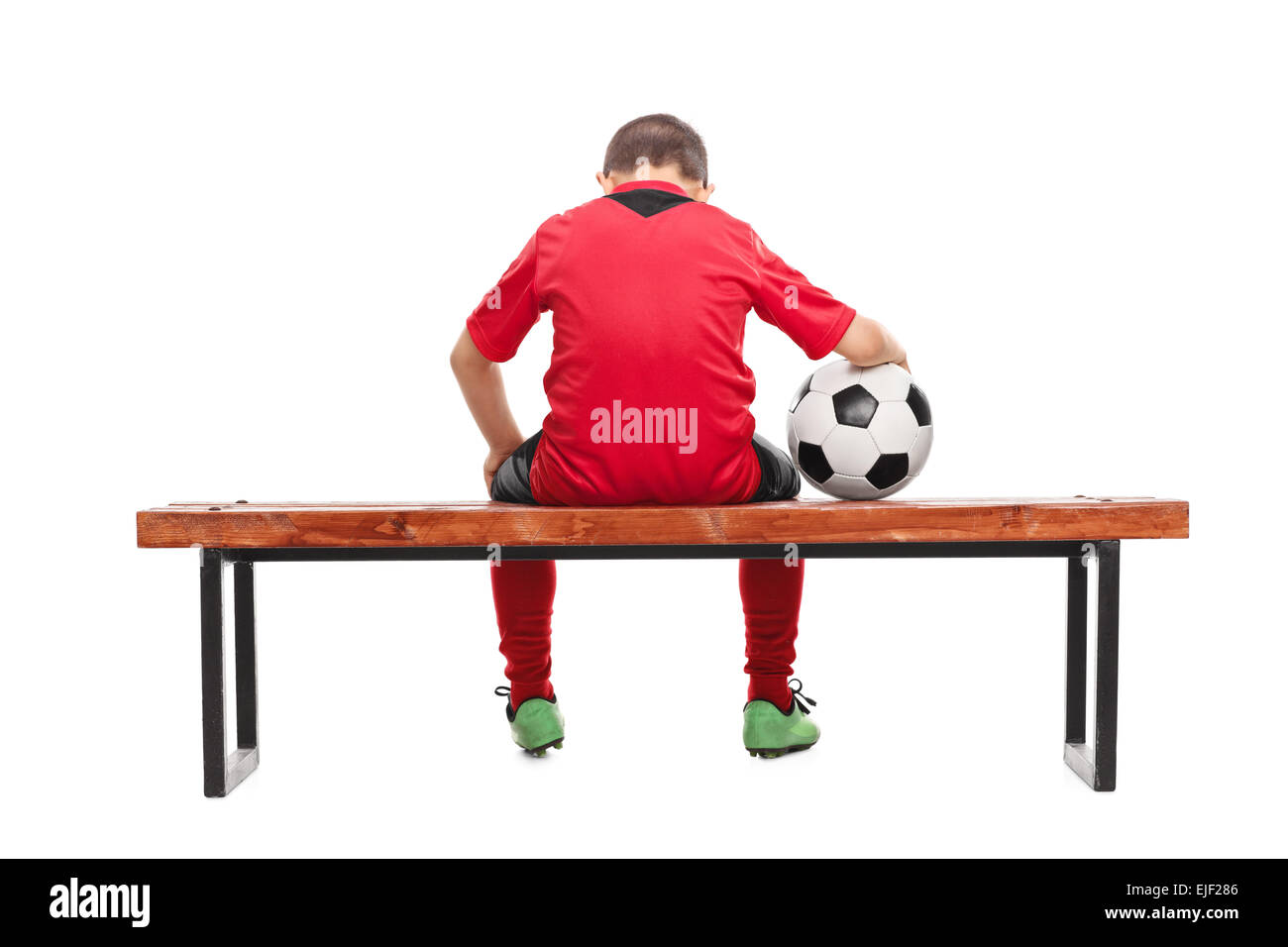 Rear view studio shot of a sad little boy in red soccer jersey seated on a bench and holding a ball isolated on - Stock Image
