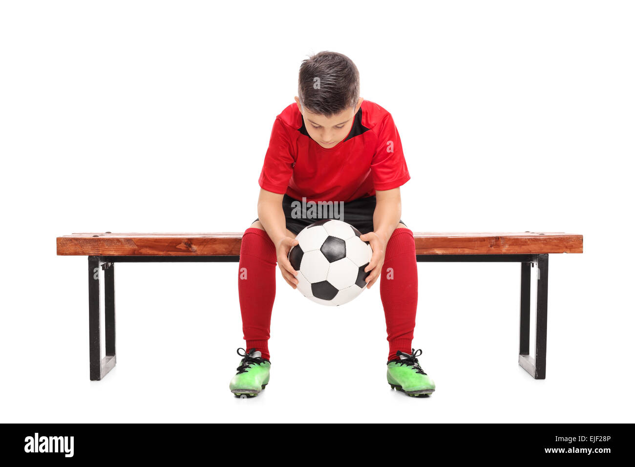 Worried little boy in red football shirt sitting on a bench and holding a ball isolated on white background - Stock Image