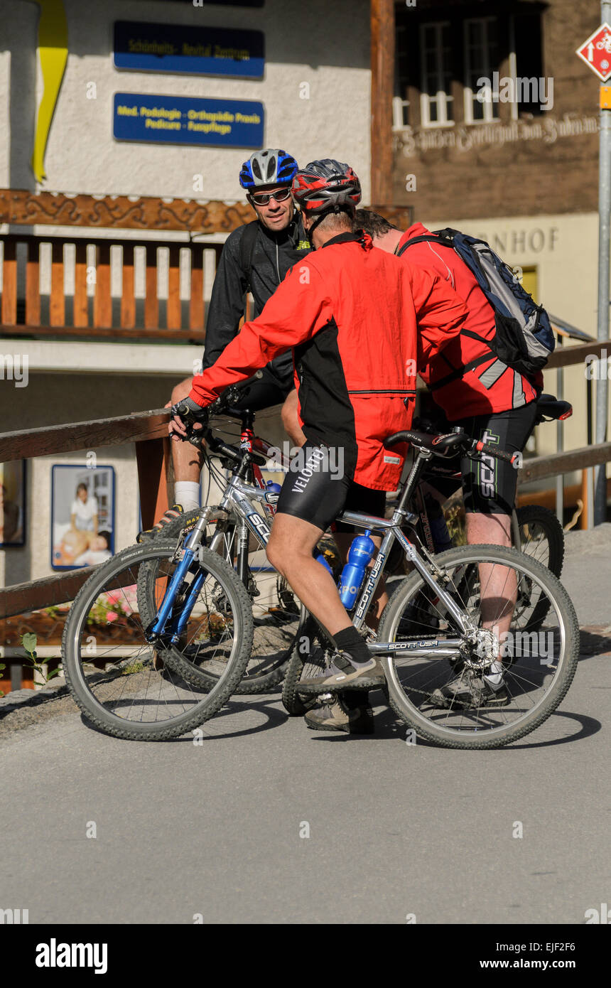 Mountain Bikers taking a break in the town of Leukerbad, in the Canton of Valais, Switzerland. - Stock Image