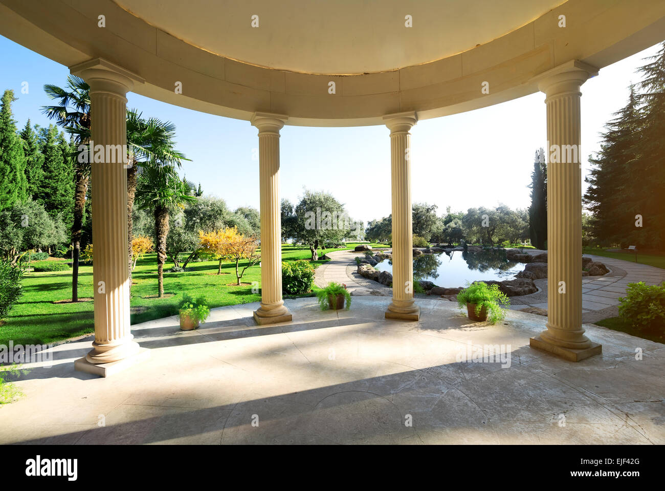 Arbour with columns near lake in the park - Stock Image