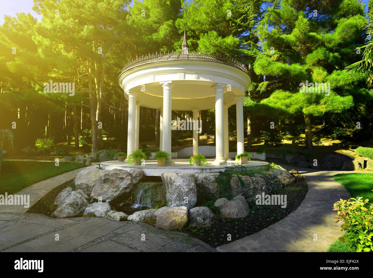 White bower among the coniferous trees in park - Stock Image