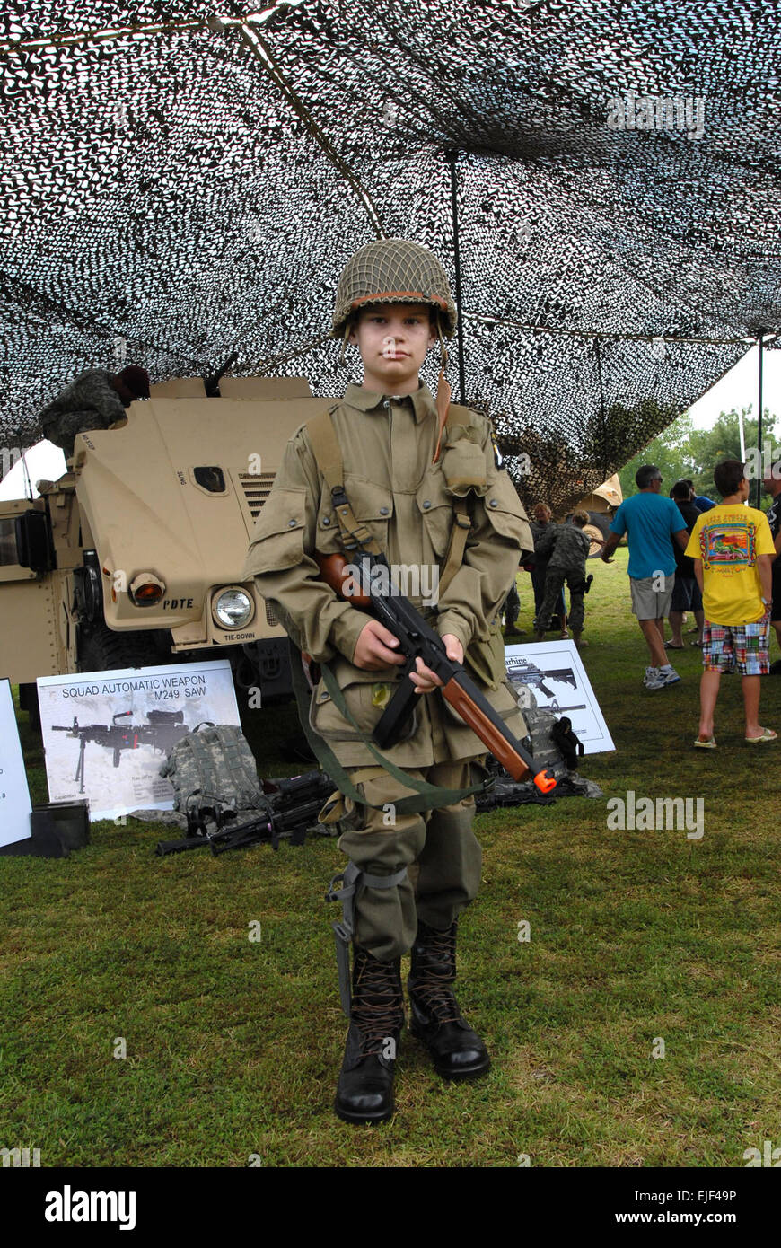 A young boy dressed in an old paratrooper uniform stands ready during the 69th National Airborne Day celebration - Stock Image