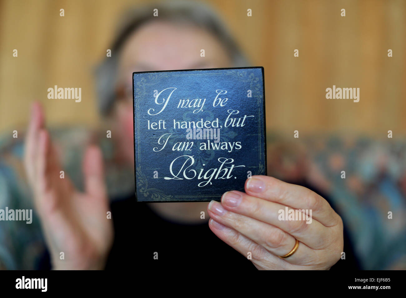 A left handed person holds a coaster inscribed with the words I maybe left handed but I am always right - Stock Image