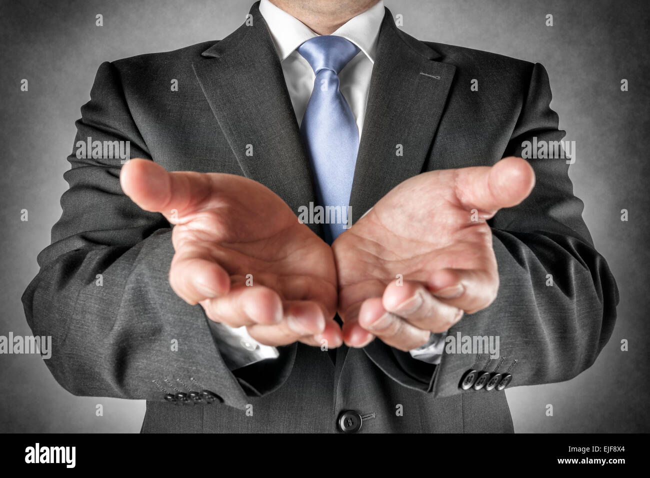 Businessman in dark suit holds out his hands - Stock Image