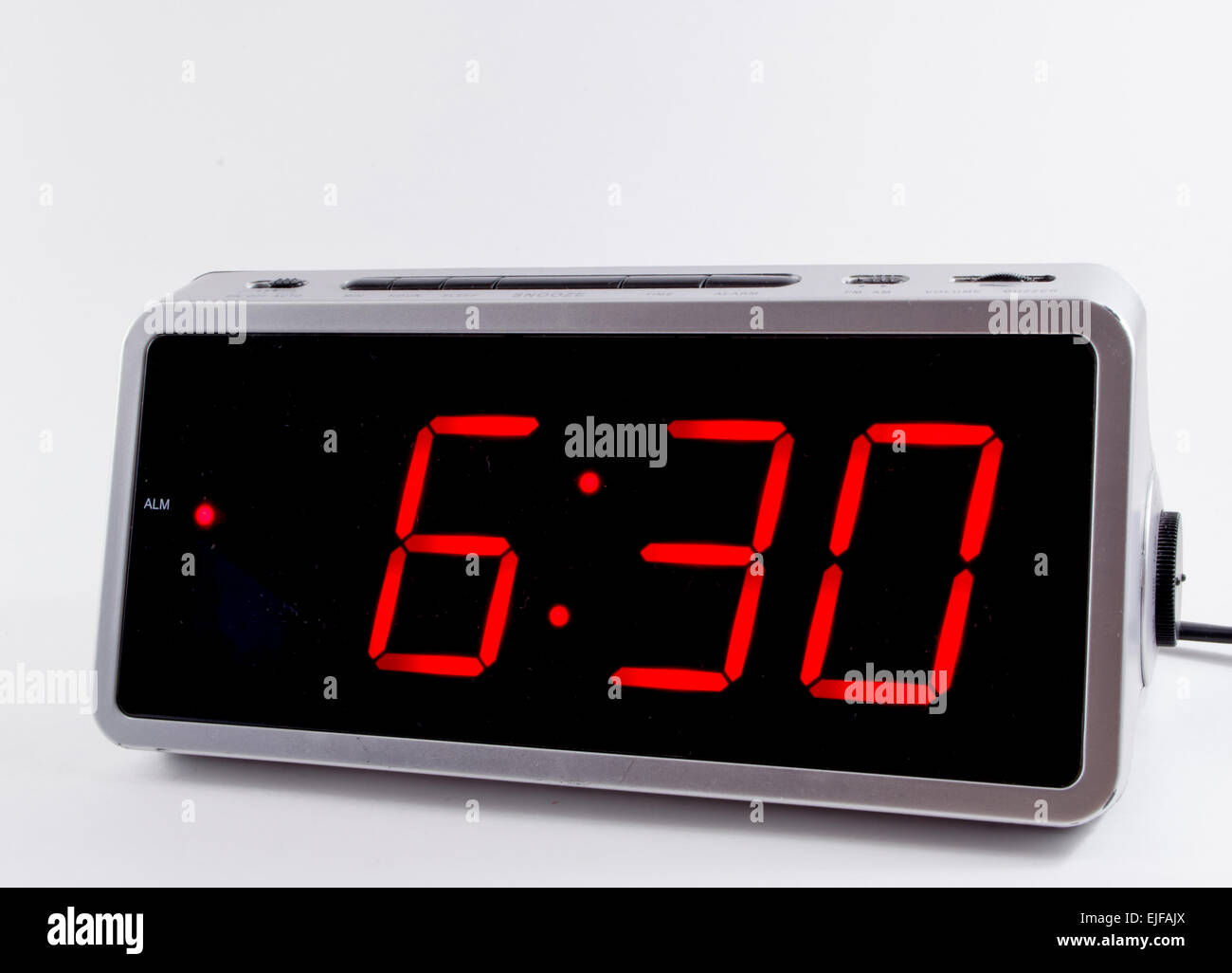 A retro looking silver digital alarm clock at six thirty 6 ...