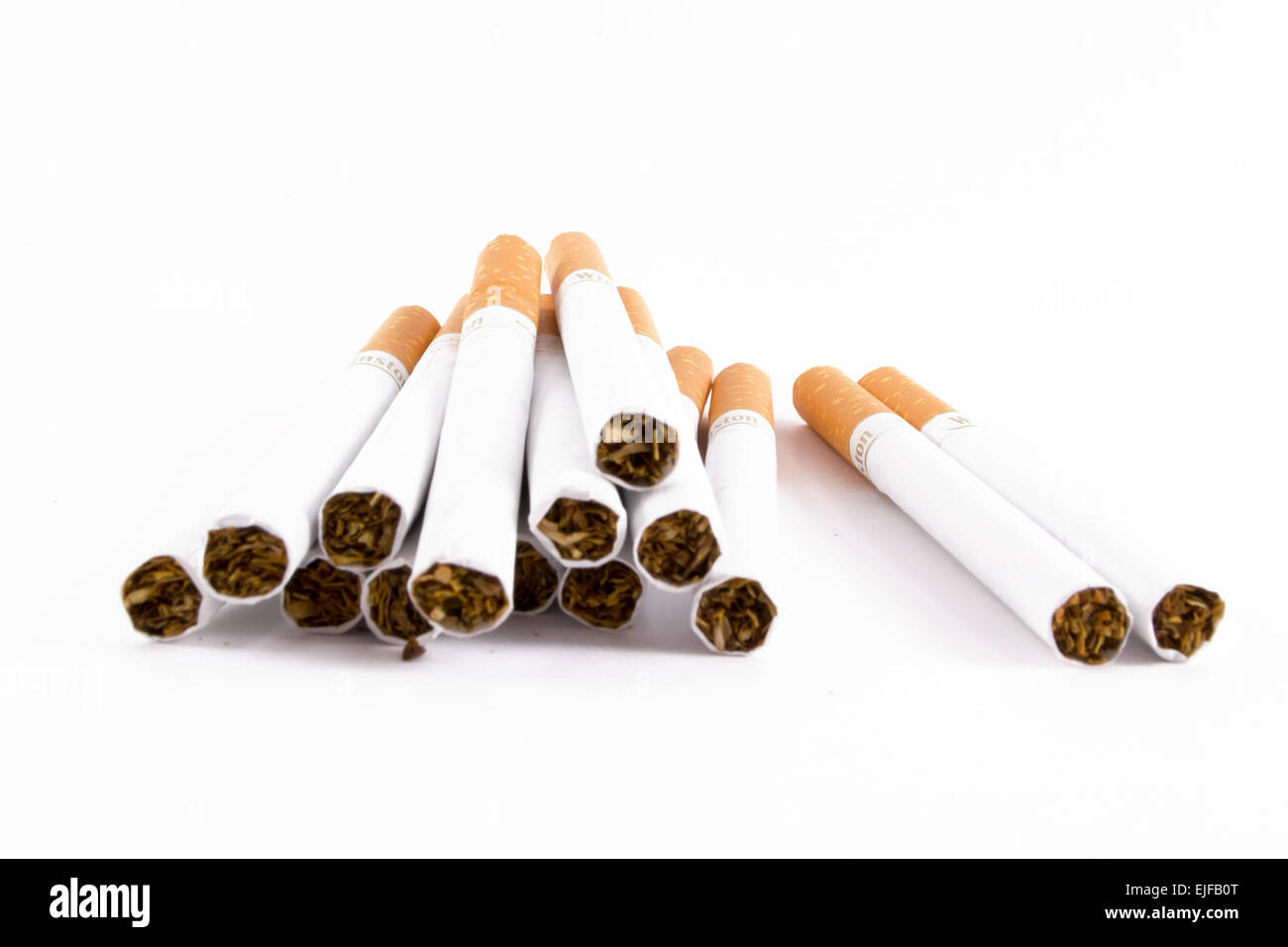 A pile of unlit cigs isolated on white in closeup - Stock Image
