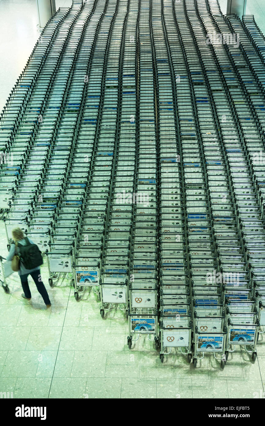 Generic shot of traveller collecting a trolley from hundreds of luggage trolleys at an airport - Stock Image