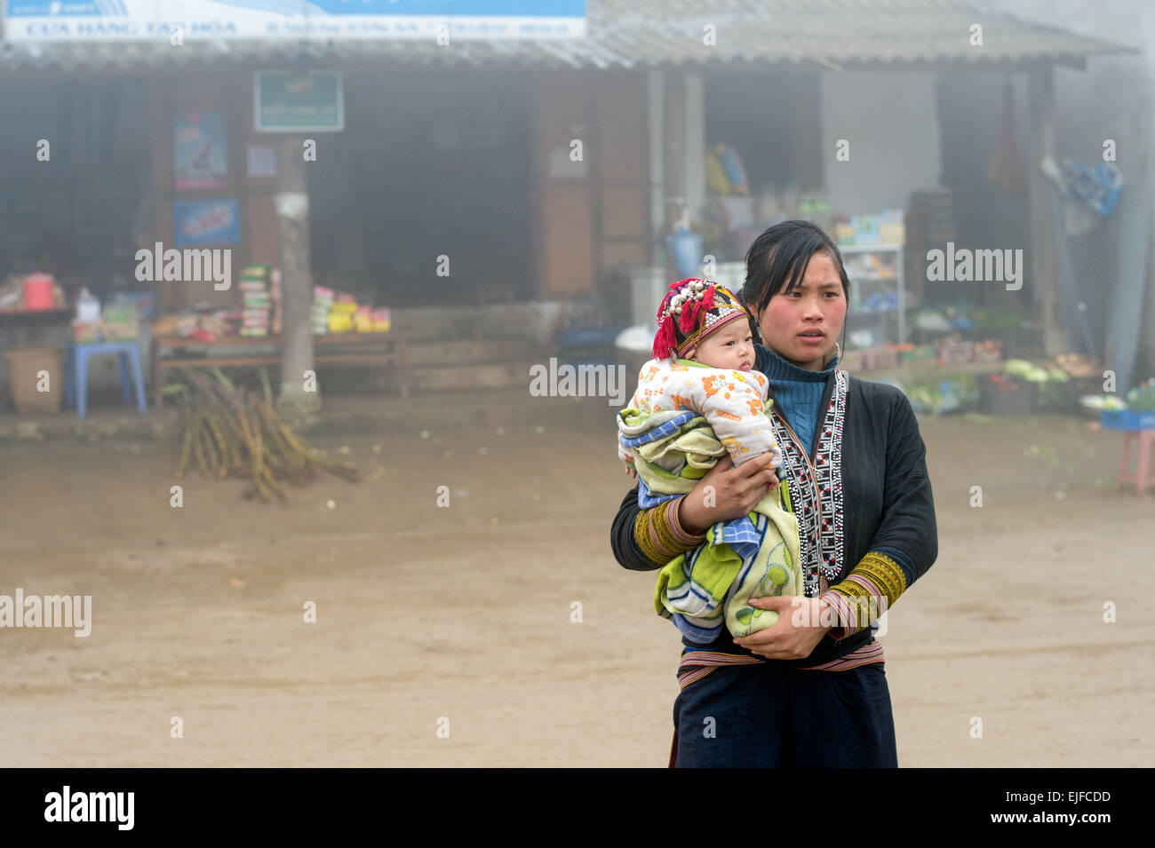 Young Red Dao woman carries a child in Ta Phin Village outside Sapa in northern Vietnam - Stock Image