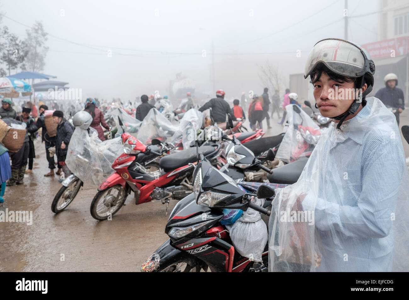Vietnamese man at the market in Sapa on a rainy day in northern Vietnam - Stock Image