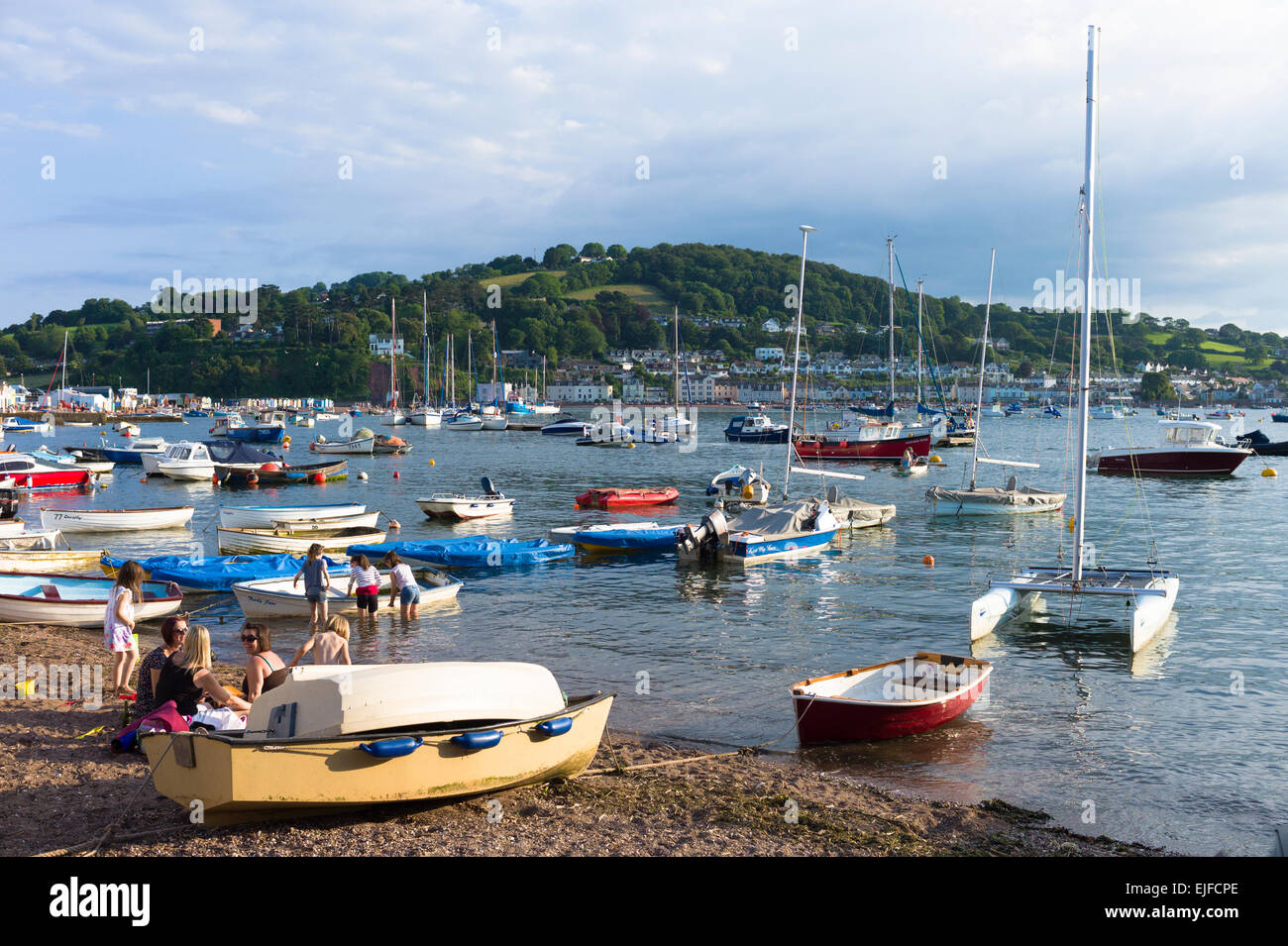Boats in the harbour and family group on beach at coastal resort of Teignmouth in South Devon, England, UK Stock Photo