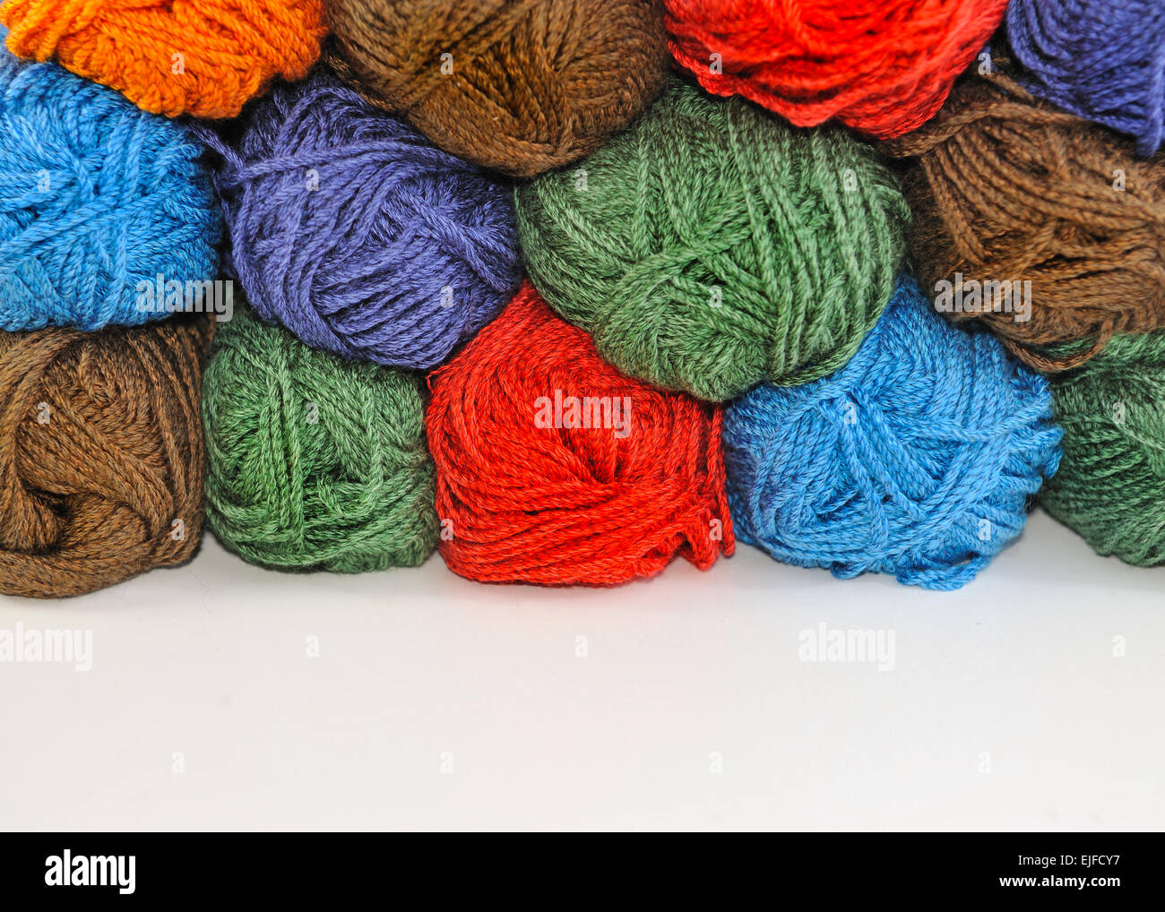 Multi-colored skeins of yarn for knitting stacked one upon the other. - Stock Image