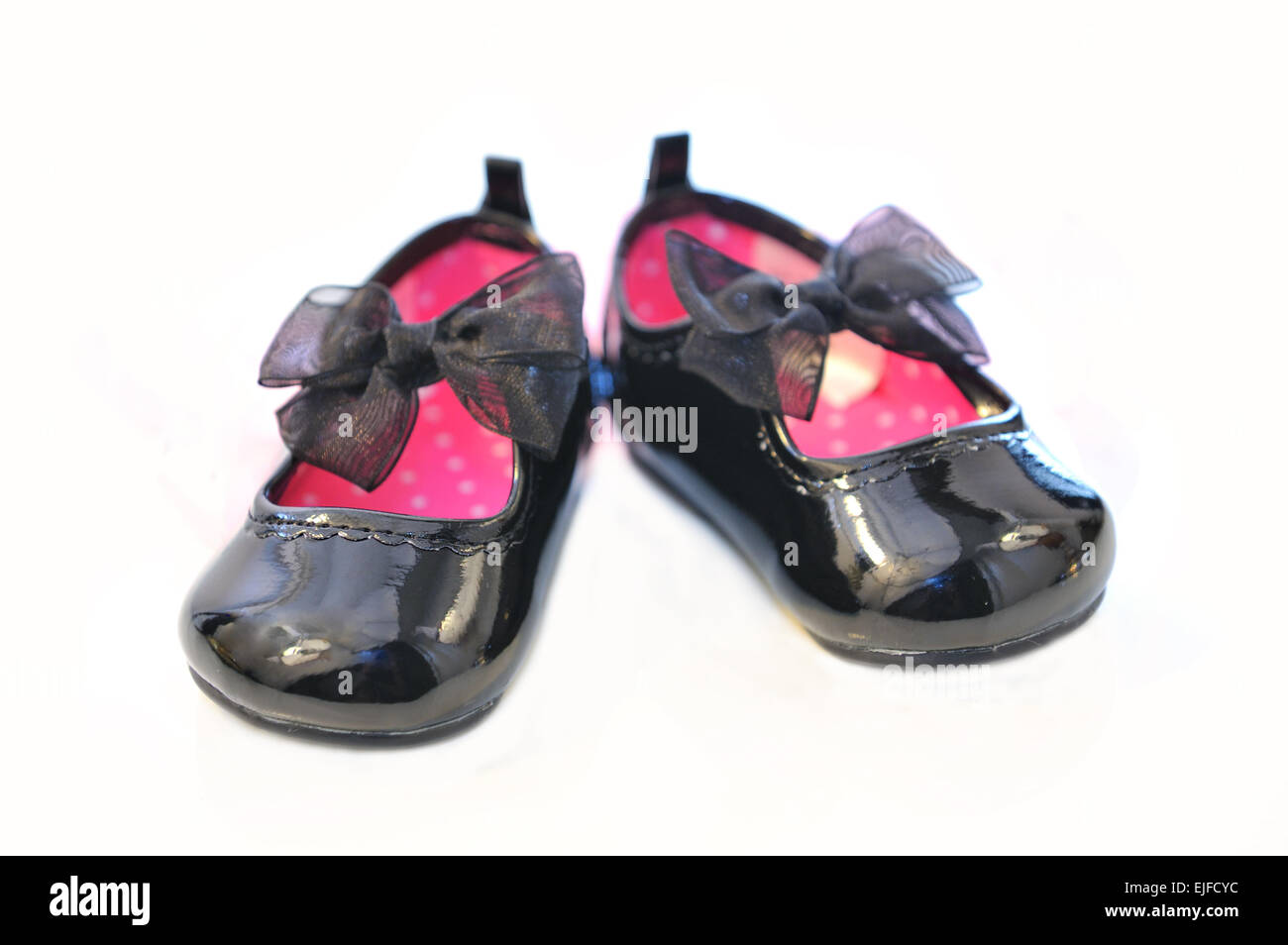 Baby girl's patent leather shoes with black ribbon - Stock Image