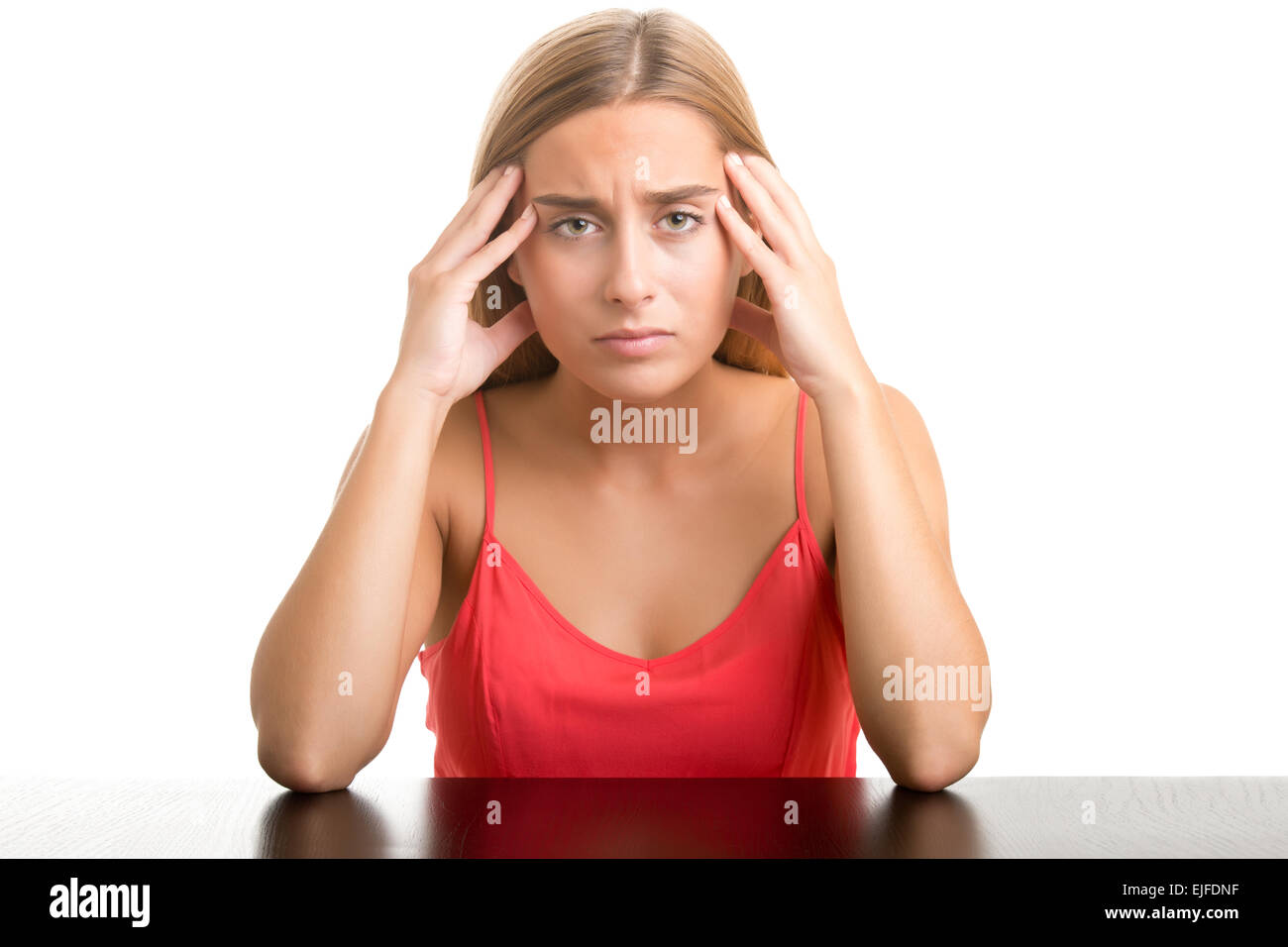 Woman suffering from an headache, holding her hand to the head, isolated in white - Stock Image