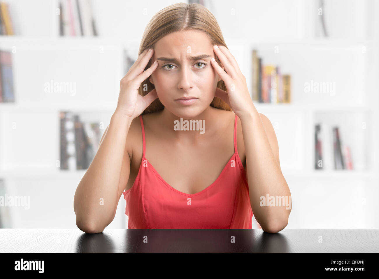 Woman suffering from an headache, holding her hand to the head, in a library - Stock Image