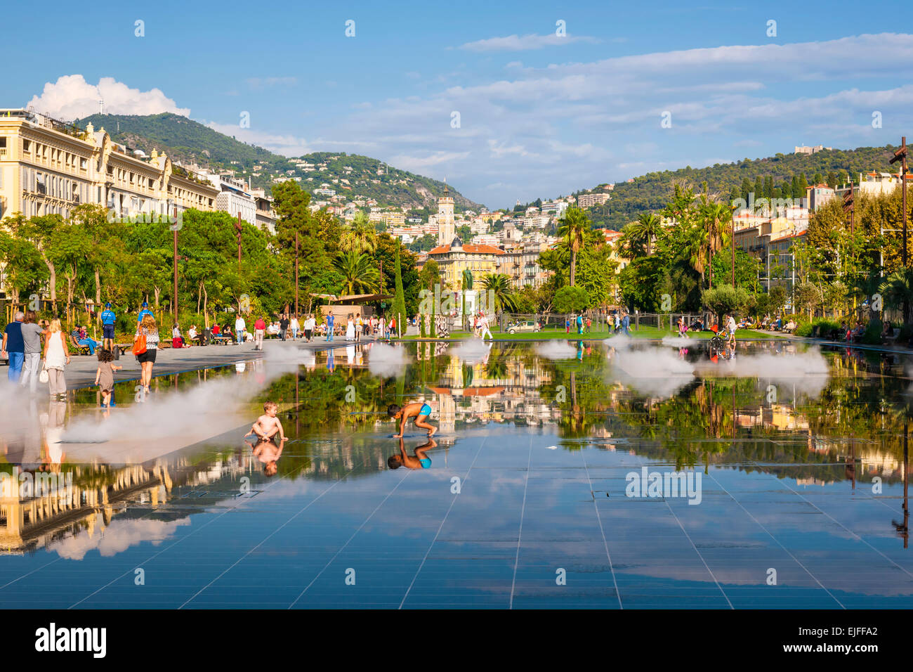 NICE, FRANCE - OCTOBER 2, 2014: Children playing in fountain on Promenade du Paillon reflecting the city and surrounding Stock Photo