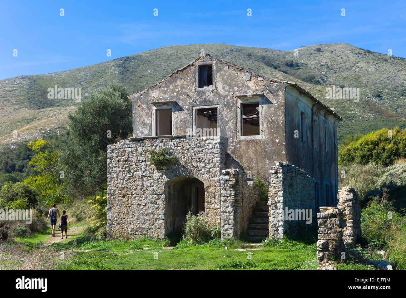Tourists visiting Skordilis Mansion house ruin in oldest village of Corfu - ancient Old Perithia - Palea Perithea, - Stock Image