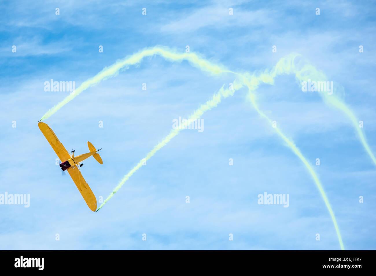 Aerobatic plane with colored smoke trails. - Stock Image