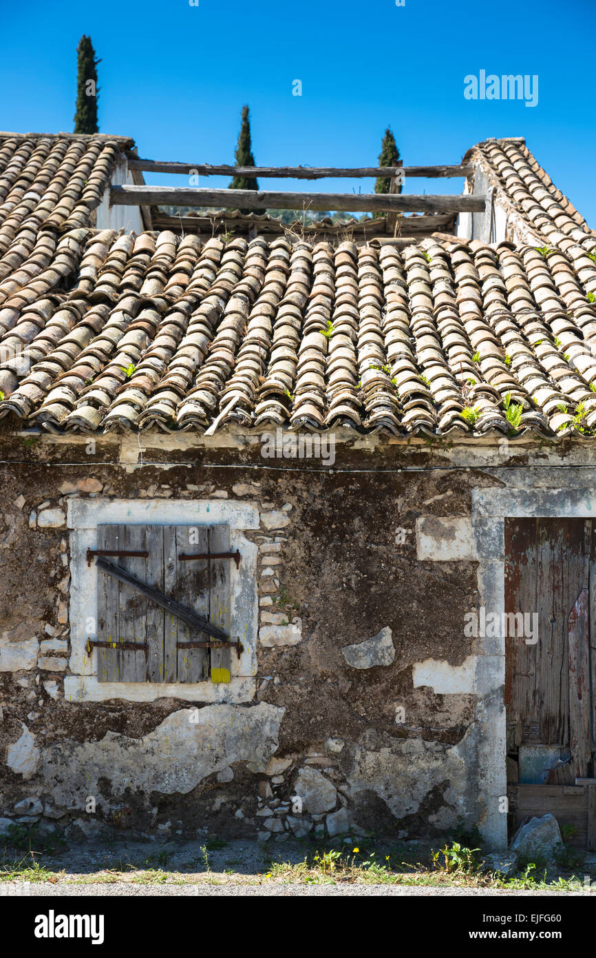 Old shabby derelict house with collapsed roof tiles and shutters in village of Perithia, Northern Corfu, , Greece - Stock Image