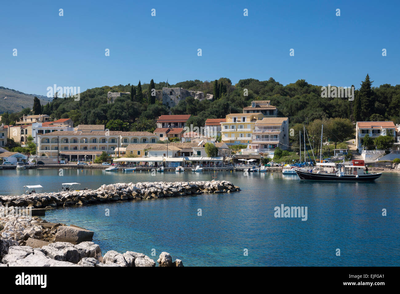 Spectacular beach resort and harbour of Kassiopi with blue sky and turquoise Ionian Sea, Corfu, Ionian Islands of Stock Photo