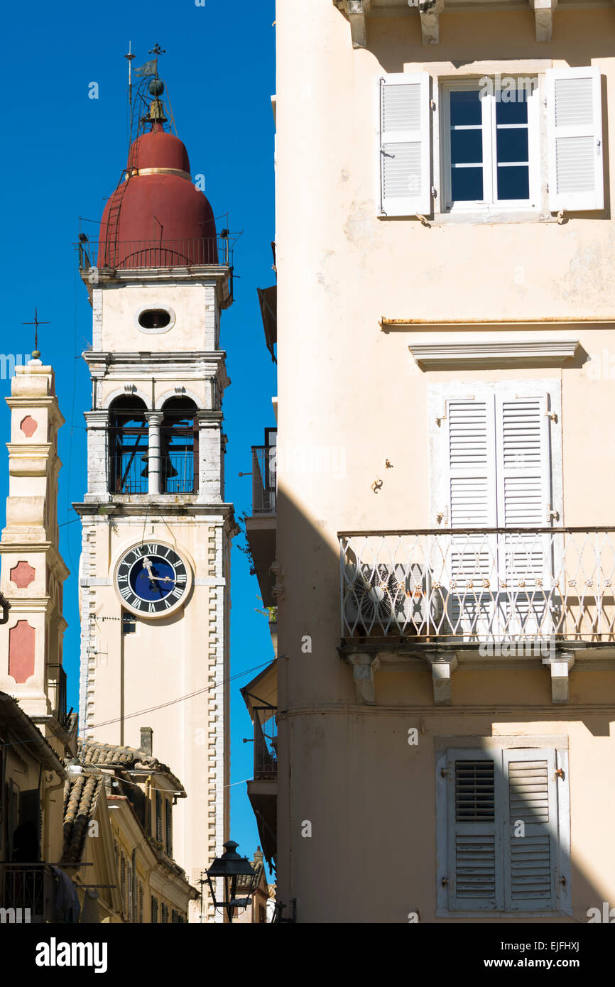 Street scene by Spianada and Church of Saint Spyridon with traditional clock belltower in Kerkyra, Corfu Town, Greece - Stock Image