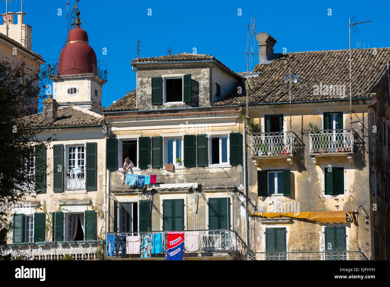 Greek woman hanging out washing on line from window of traditional apartment in Kerkyra, Corfu Town, Greece - Stock Image