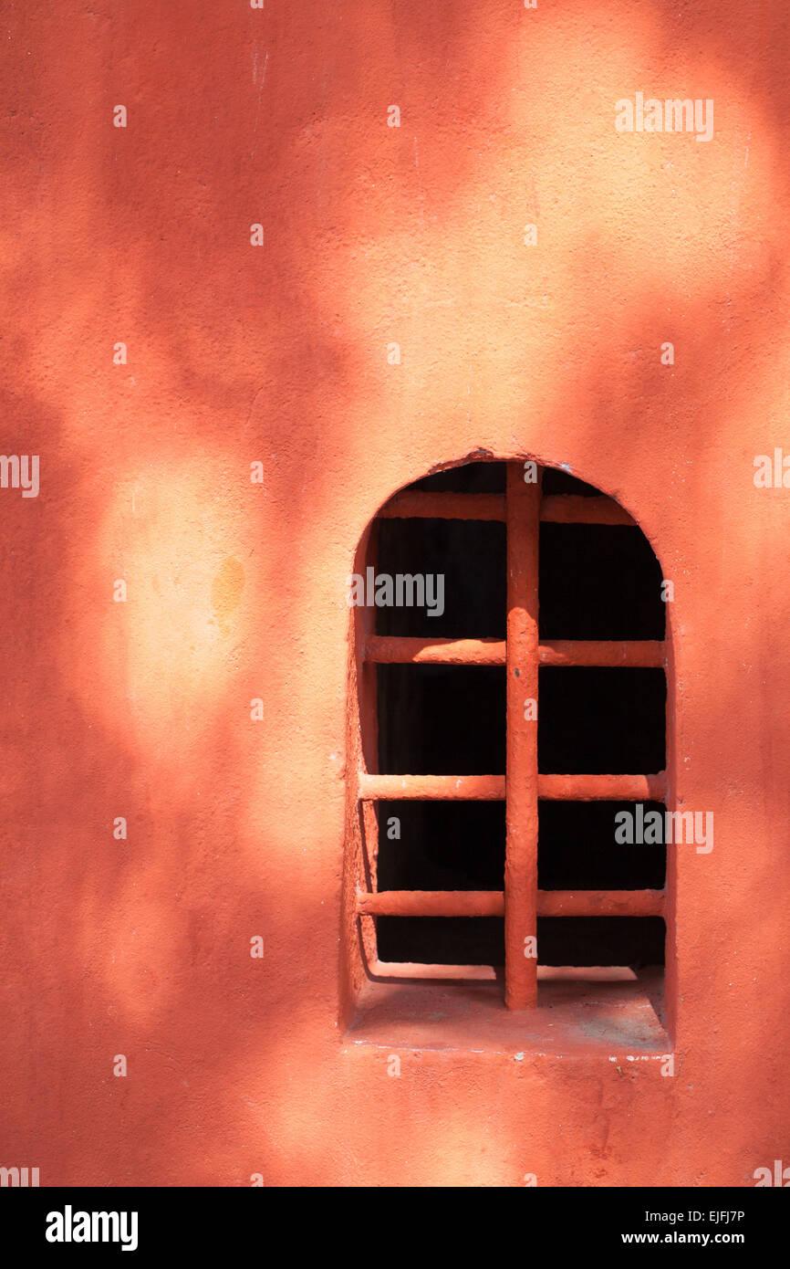 Sun dappled orange stucco wall and window - Stock Image