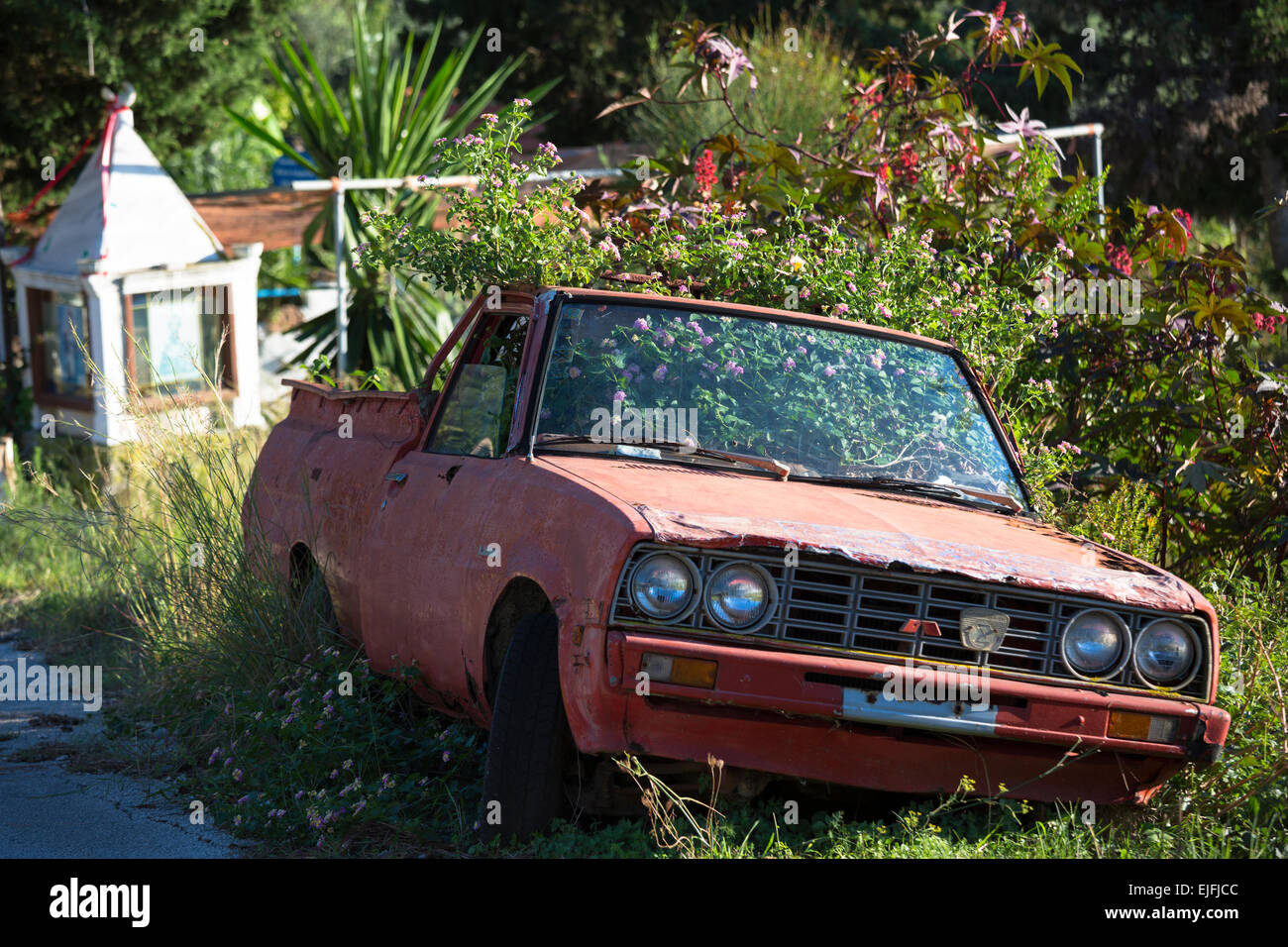 Derelict rusty car, a sign of economic crisis and downturn, in Corfu, Greece - Stock Image
