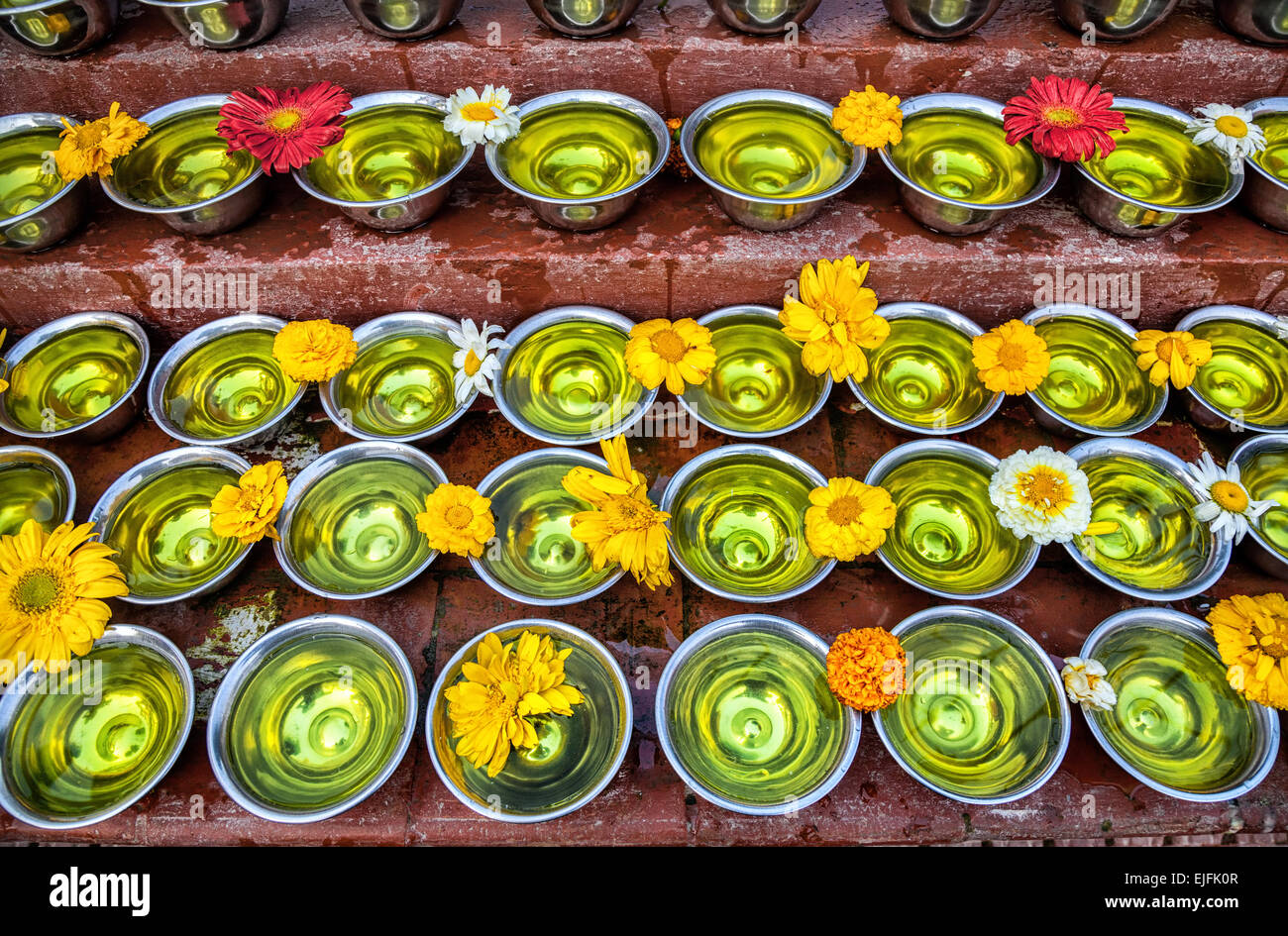 Bowls with saffron water and flowers at Bodhnath stupa in Kathmandu valley, Nepal - Stock Image