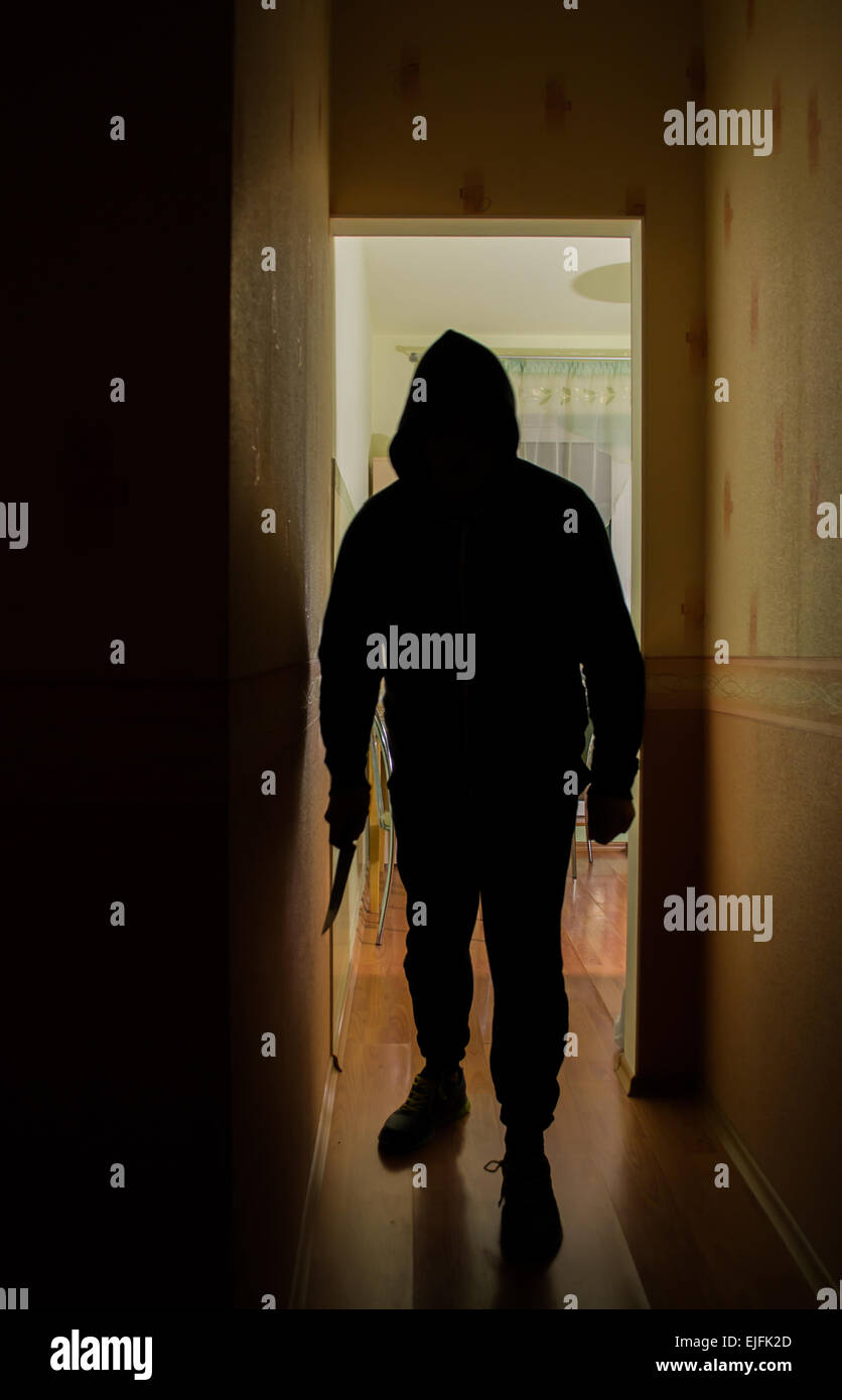 A burglar man with a knife in darkness - Stock Image