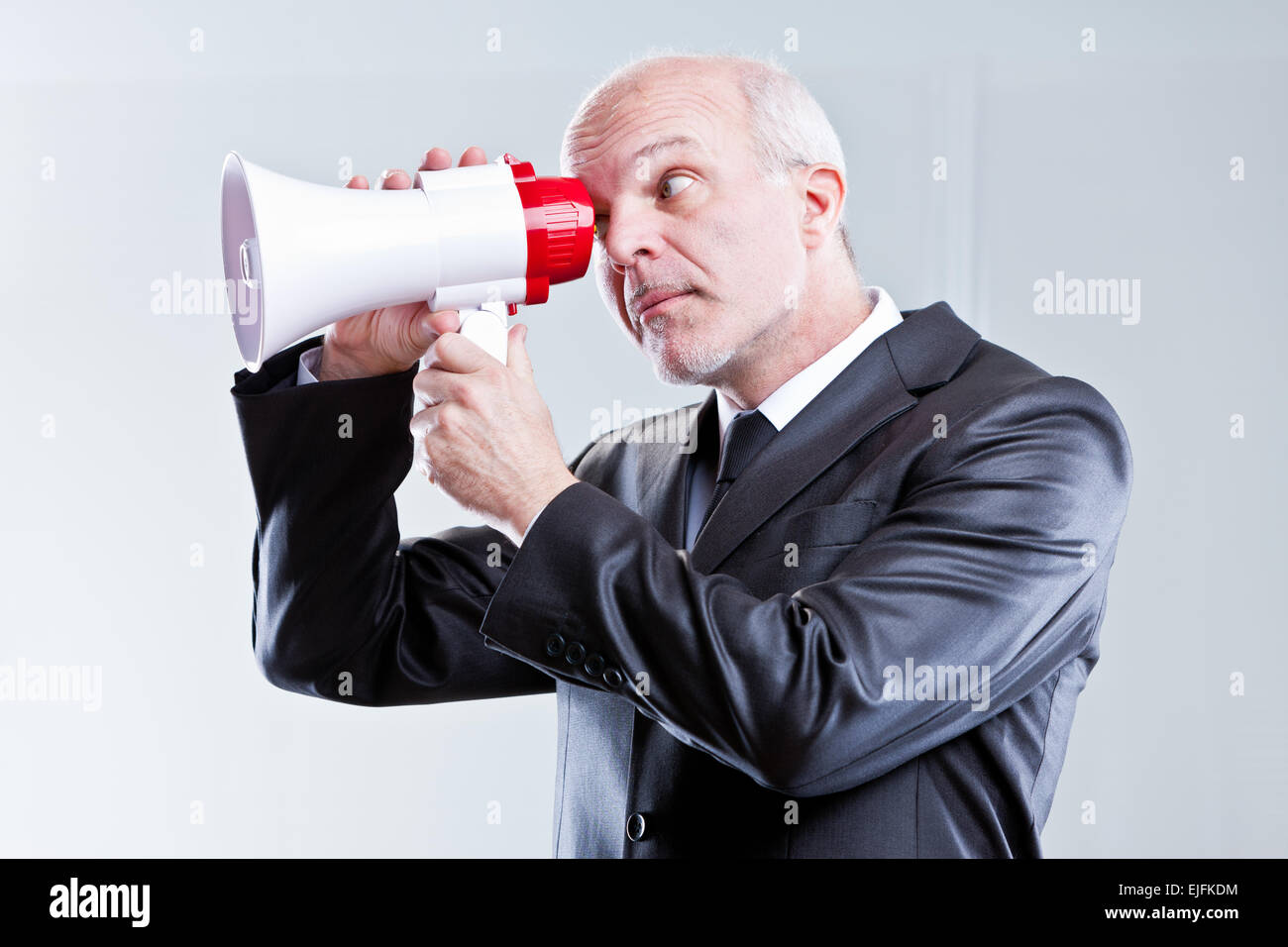 man using a megaphone in an unfitting way - Stock Image