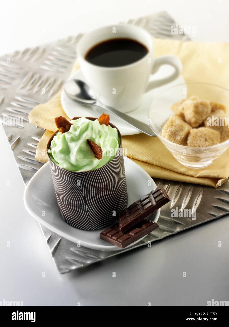 mint mousse cake in a decorated chocolate case with coffee - Stock Image