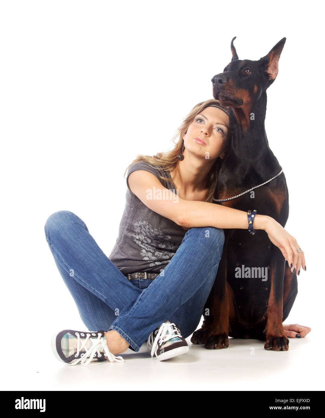 Young woman with black dobermann dog, on white - Stock Image