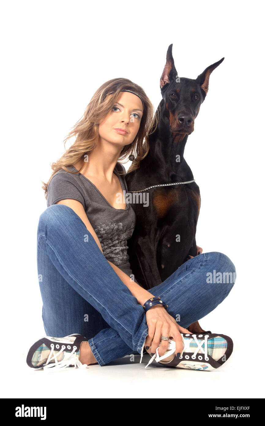 Young woman with black dobermann dog, isolated on white - Stock Image