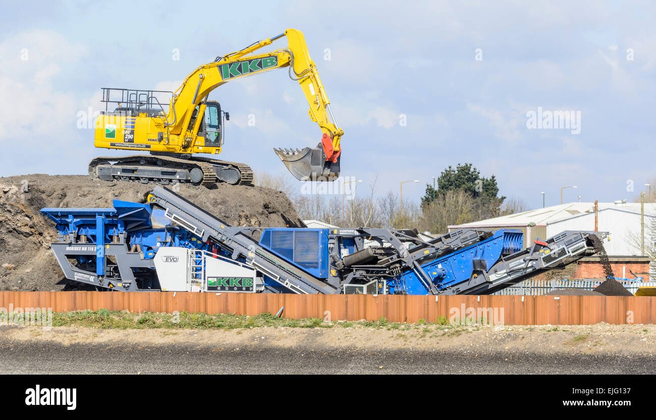 Mechanical digger on an earth mound with earth carrying conveyor belt. - Stock Image