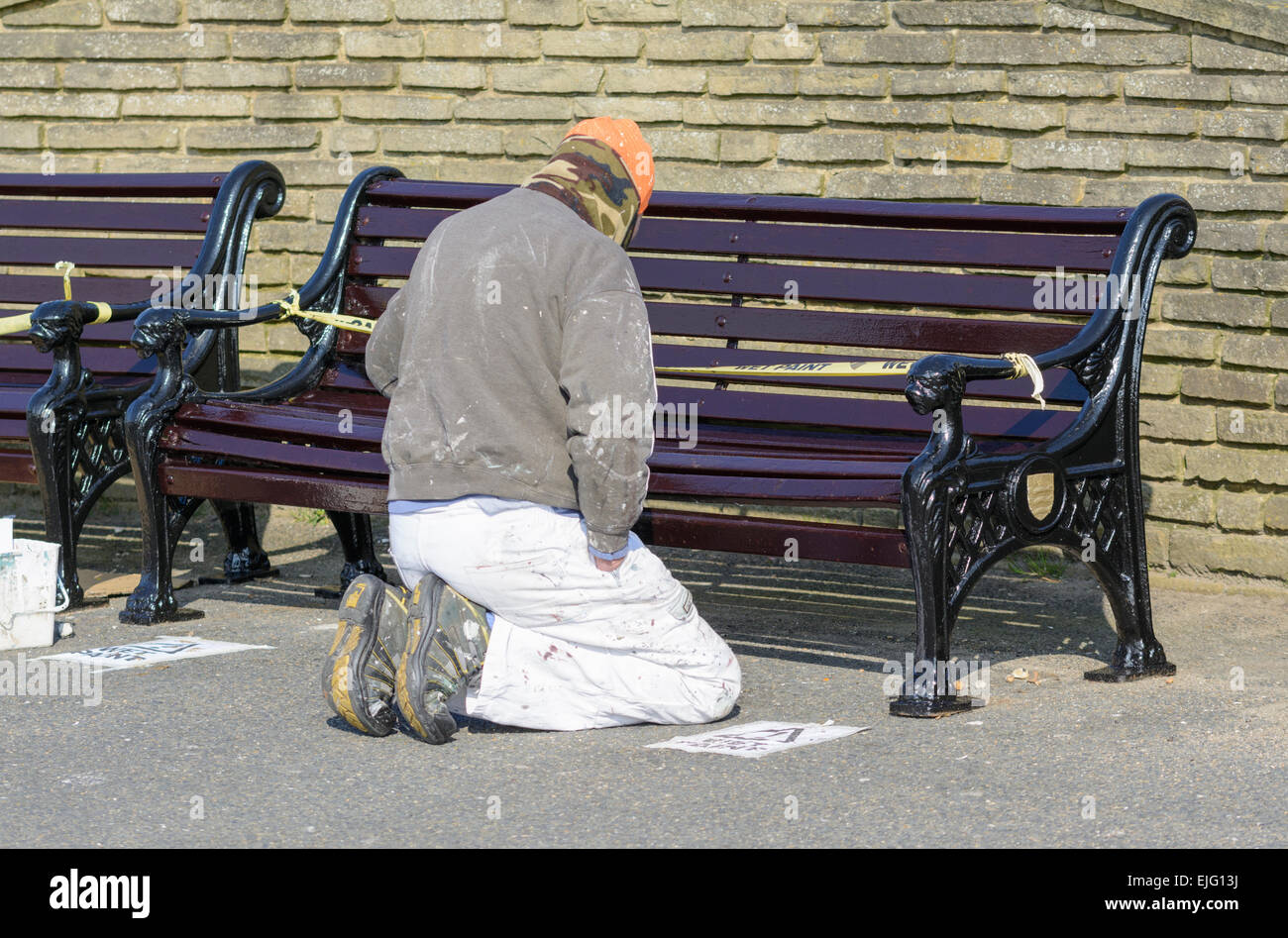 Workman kneeling down painting a wooden bench. - Stock Image
