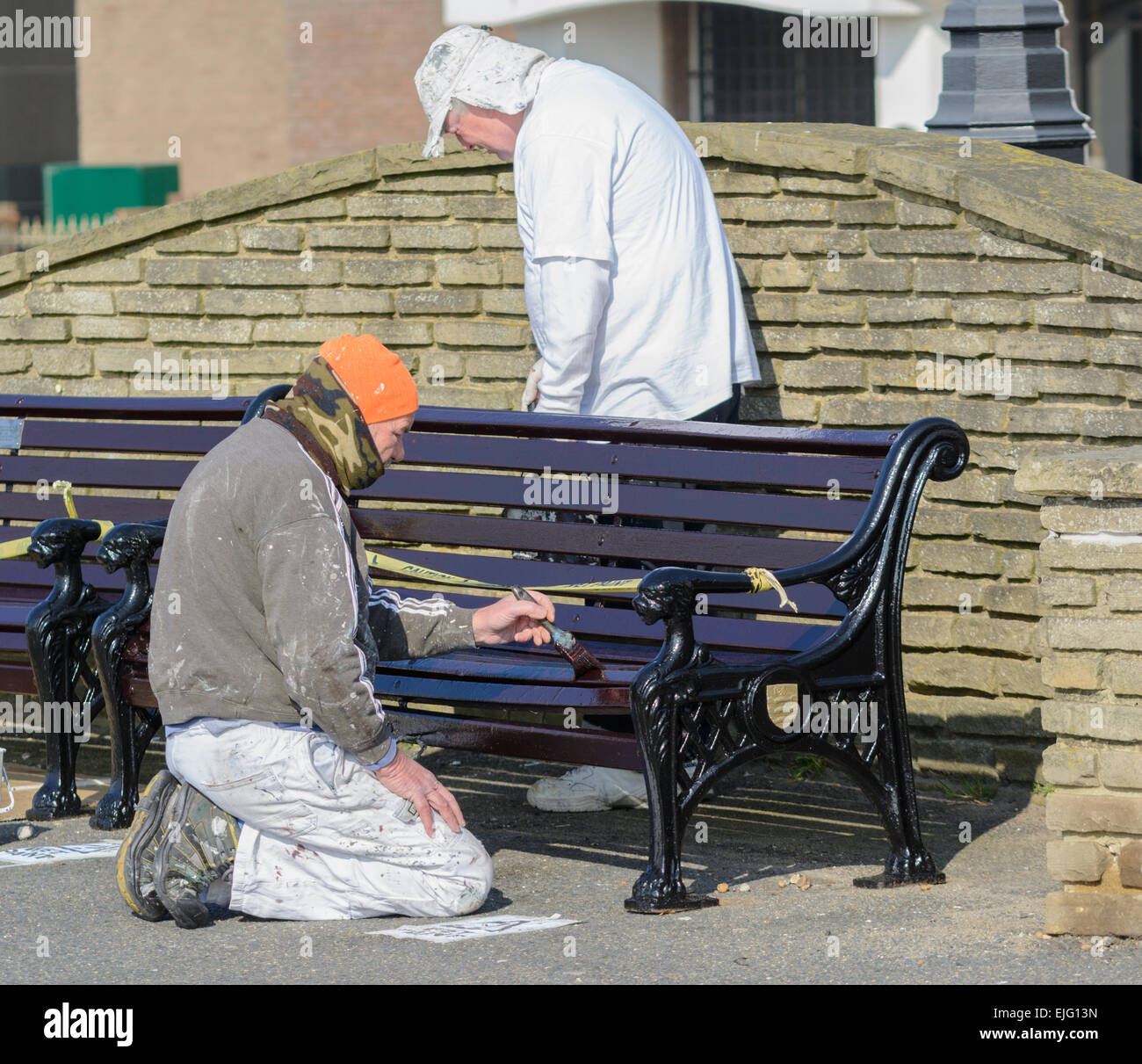 Workmen painting a wooden bench. - Stock Image
