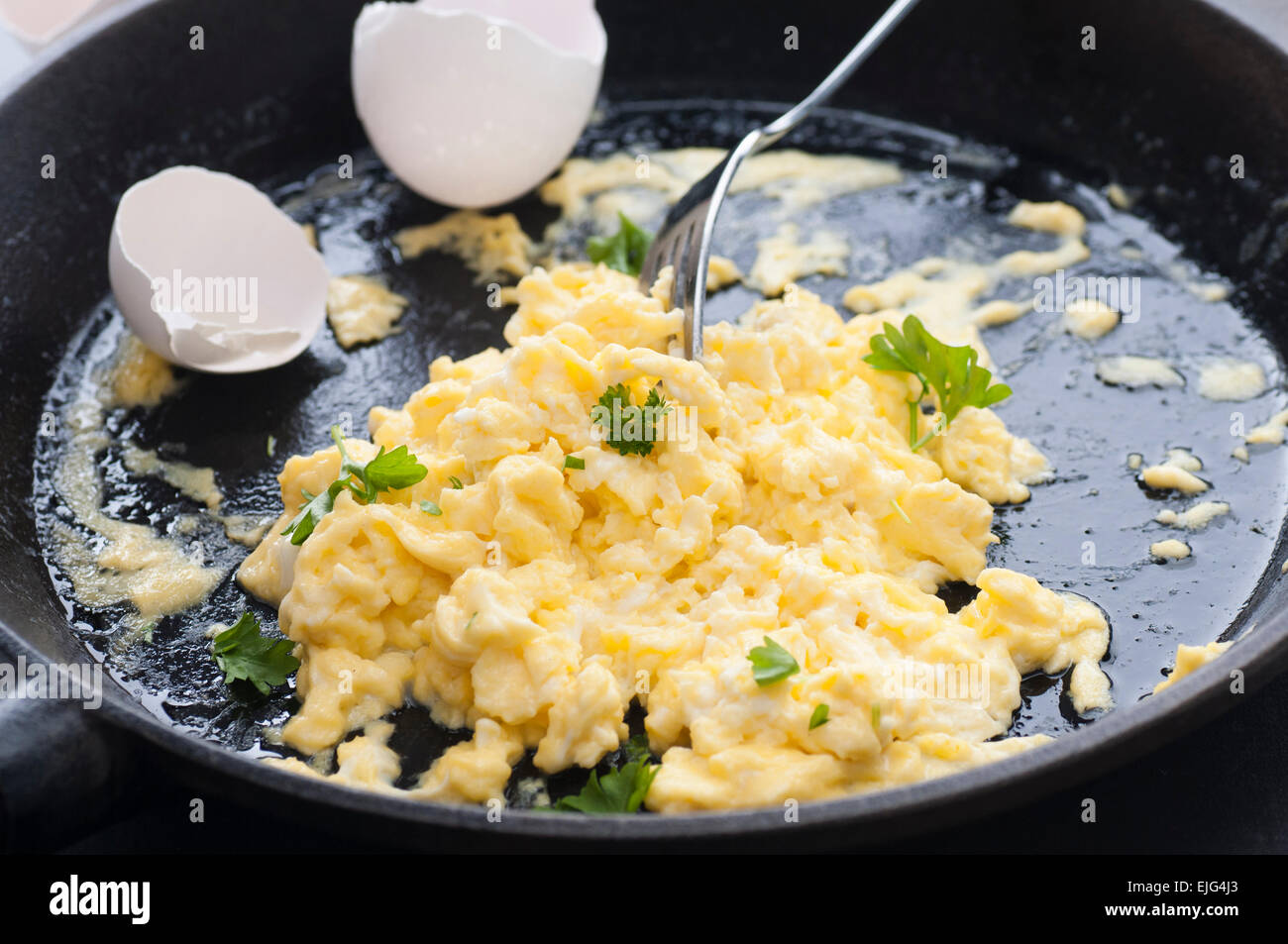 Eggs scrambled with double cream, fried in butter. All organic. Parsley on top. - Stock Image